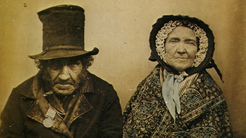 An image from the 1860s of an elderly man in a top hat and coat to the left, and an elderly woman wearing a bonnet and shawl on the right.