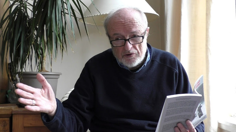 Image of Tom Leonard, a man with white hair and beard, wearing a blue jumper and holding a book, while gesticulating with his left hand.