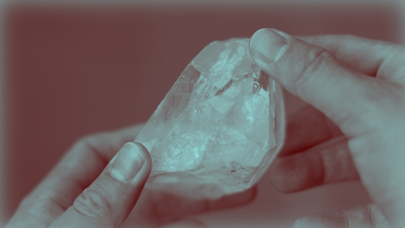 Two hands hold a crystal, with the thumbs facing upwards. The image is in shades of purple and light blue.
