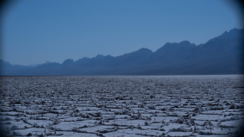 A mostly blue and purple image shows salt mines in the foreground and mountains / sky in the background.
